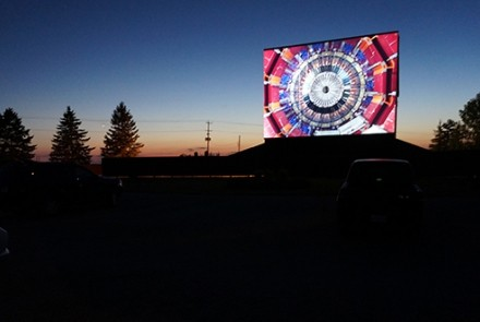 Movie on drive in screen at sunset